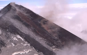 The eruption of a 8,261-foot volcano along the Alaska Peninsula southwest of Anchorage continues to dribble molten rock down its slopes, trigger steaming lahars and spit small ash clouds into the air.